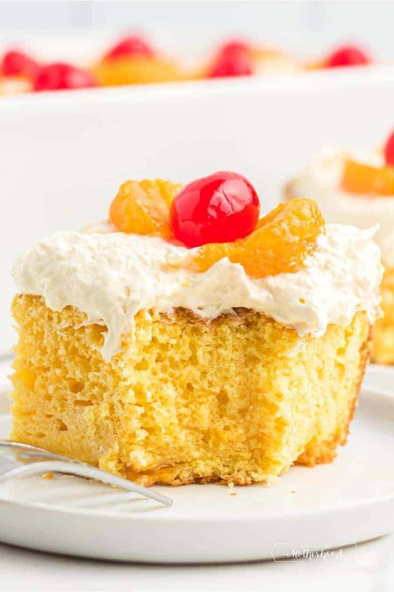 big slice of golden cake with white frosting and mandarin oranges and a cherry on top