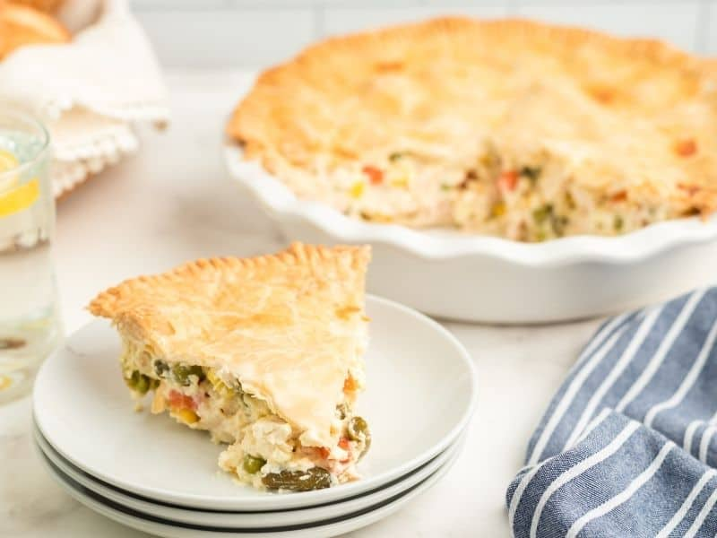 slice of chicken pot pie on white plate with remainder of the pie in the background