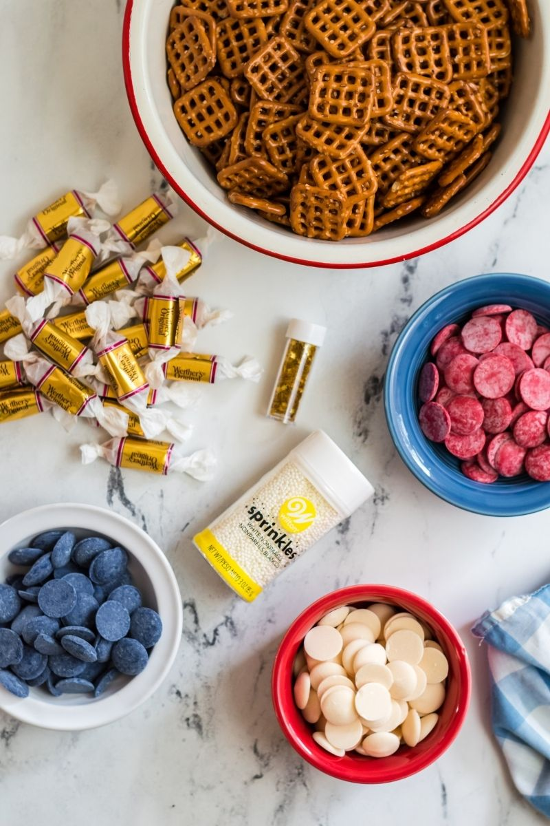 bow of pretzels, red candy melts, white candy melts, blue candy melts, caramels in wrappers, white sprinkles jar, and edible gold stars on counter