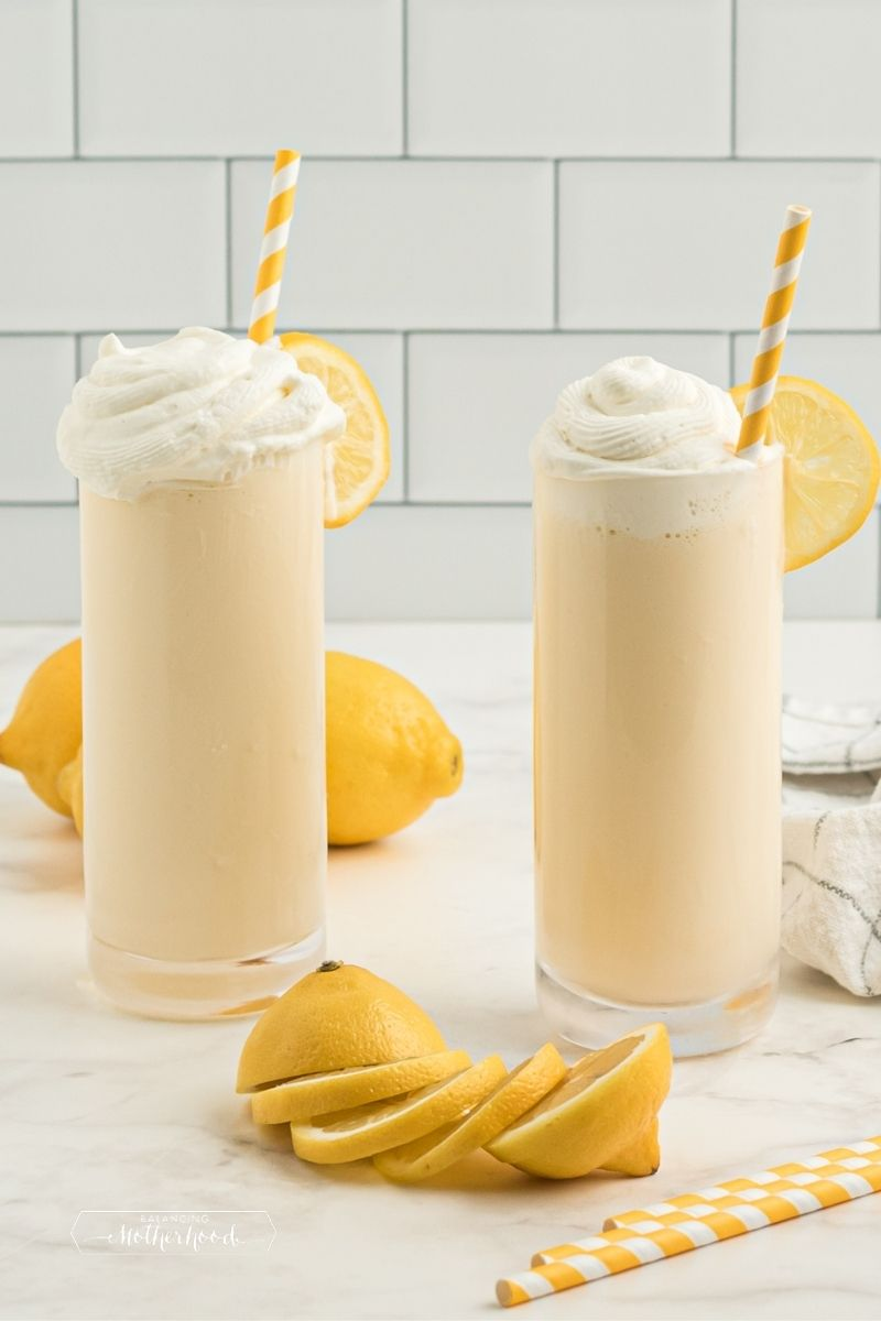 two glasses with yellow frosted lemonades with whipped cream and a yellow and white straws