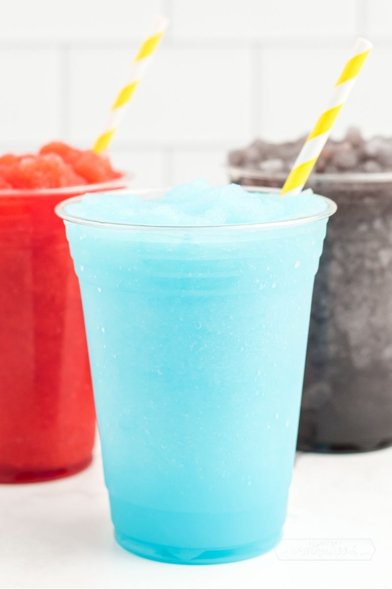 light blue slushie in plastic cup with yellow and white straw; red and purple slushies in background