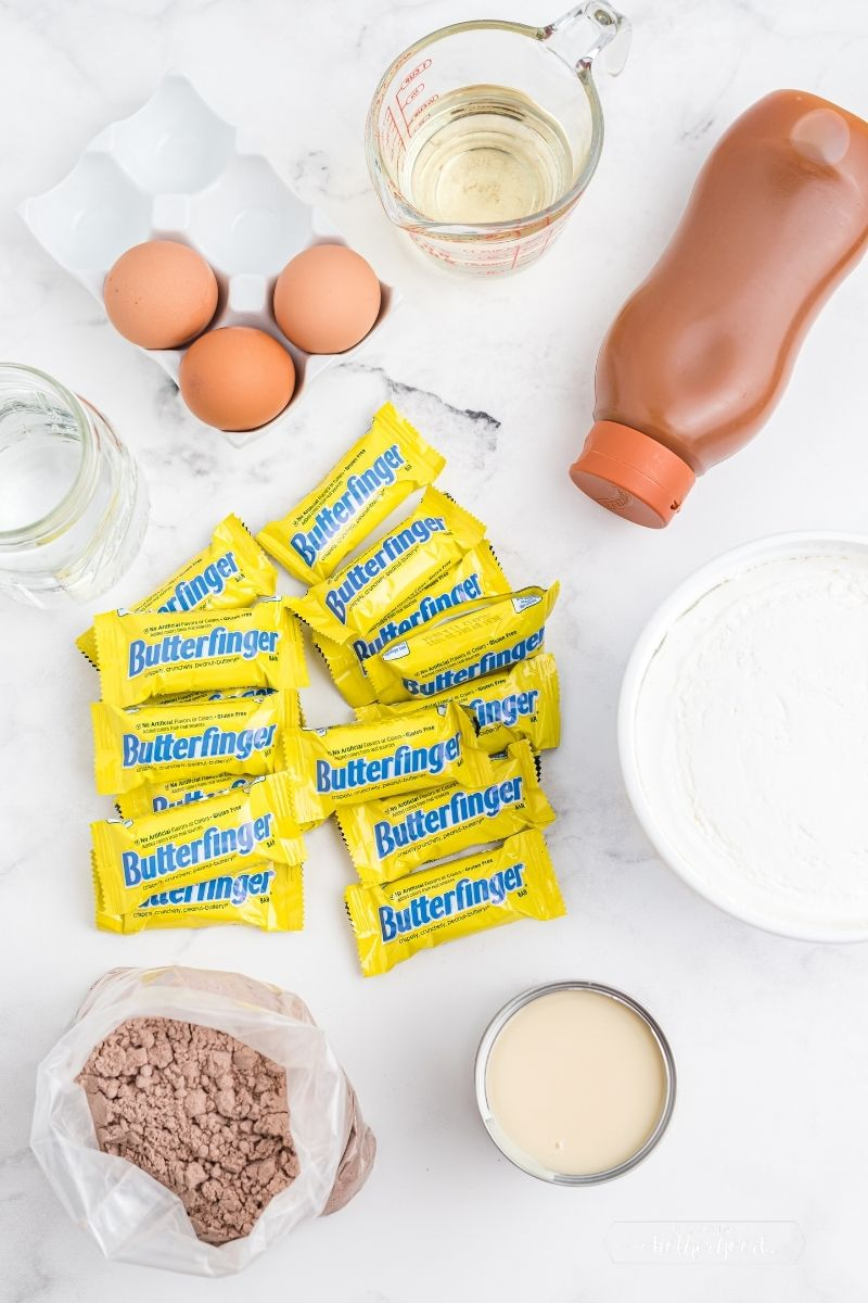 ingredients on white counter: three eggs, oil, caramel sauce, tub of Cool Whip, mini Butterfinger candy bars in wrappers