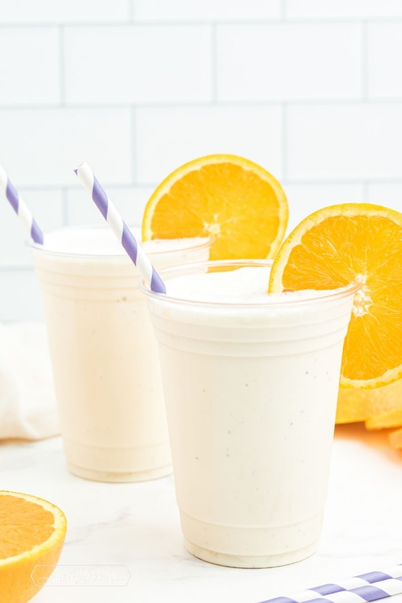 two cups with white milkshake and orange slices on side of cup with blue and white straws