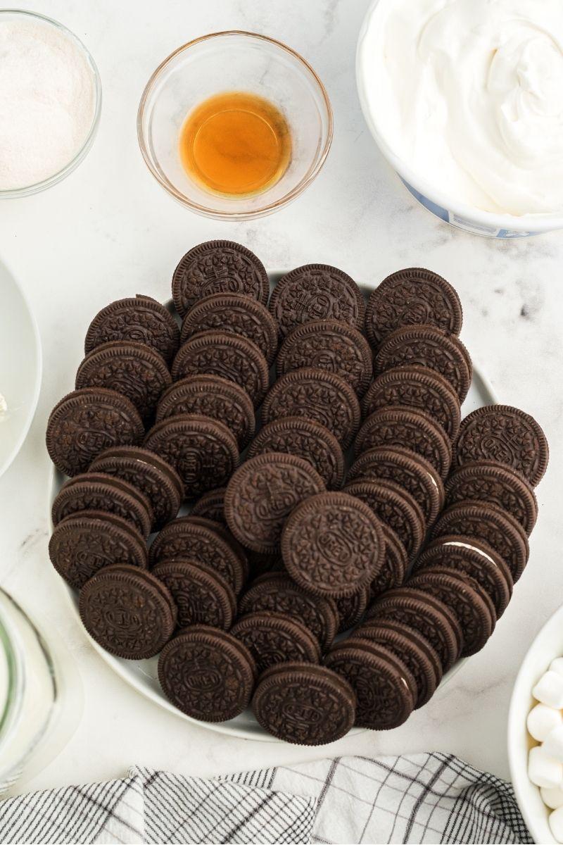 ingredients on white counter: oreo cookies, vanilla pudding, cream cheese, vanilla, milk, Cool Whip, and mini marshmallows