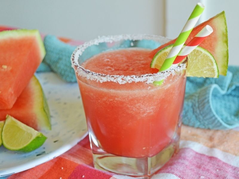cocktail class rimmed with salt and has pink watermelon margarita in it with lime wedge and a piece of watermelon with a green and white straw
