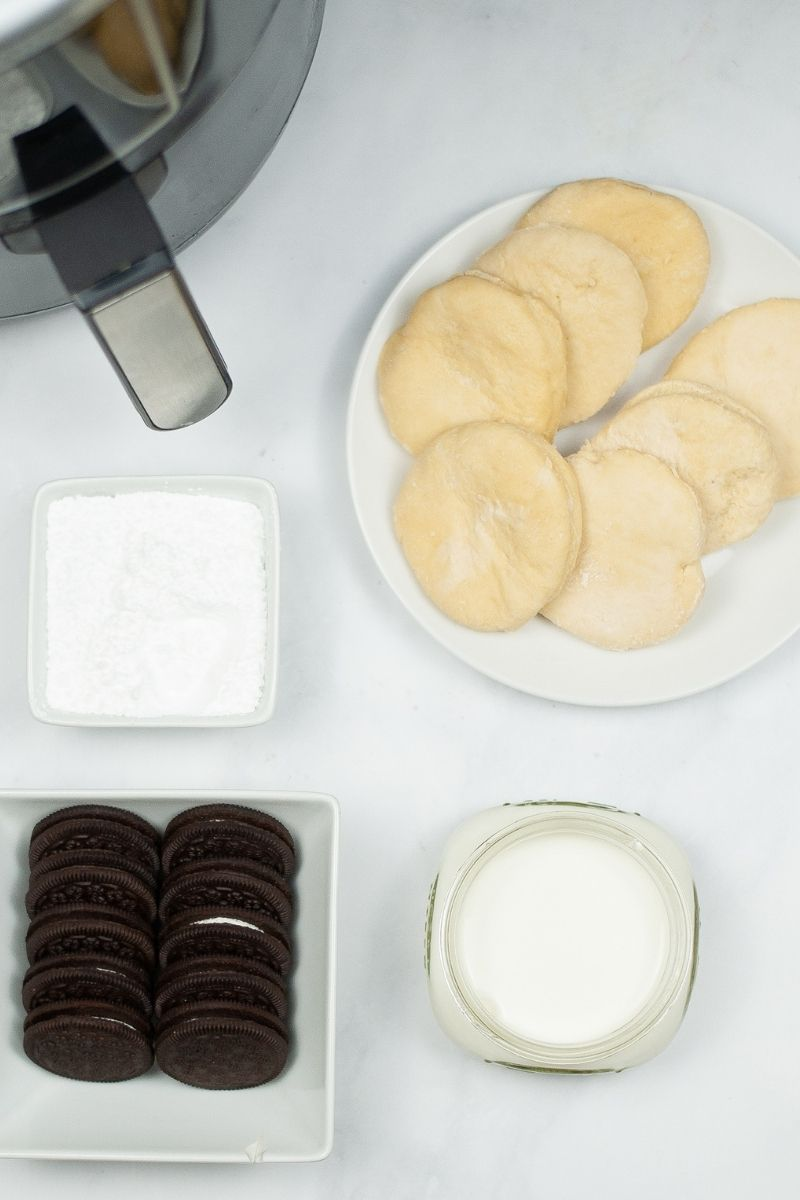 white counter with air fryer, biscuits, powdered sugar, Oreos, and milk