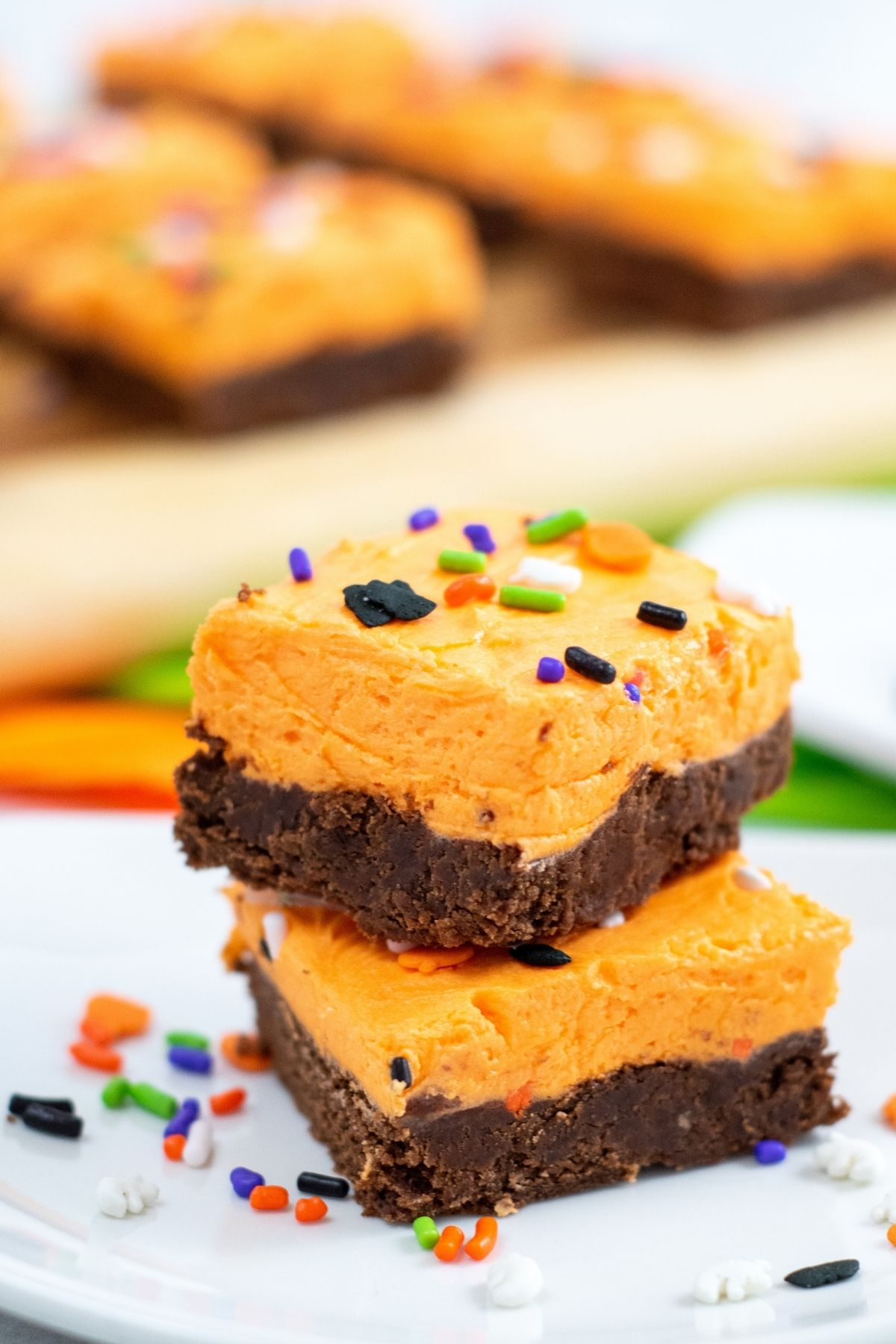 Two square chocolate cookies with thick orange buttercream and Halloween sprinkles.