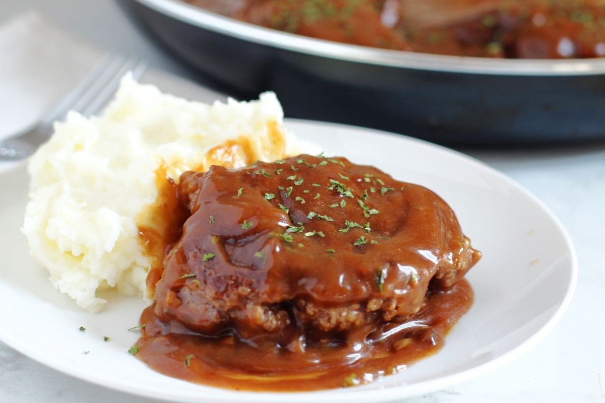 white plate with brown gravy covered salisbury steak with mashed potatoes on the side