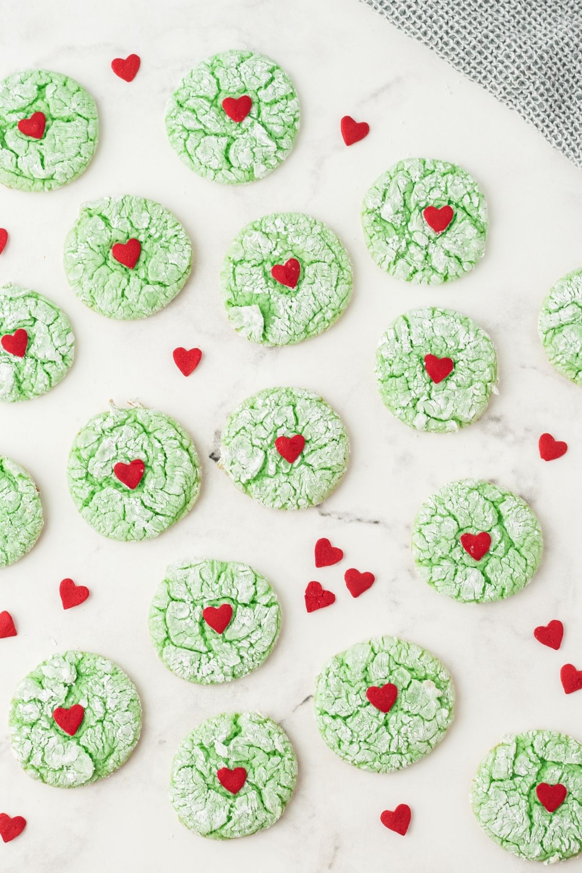 baked green cookies with cracks and a big red heart on white counter