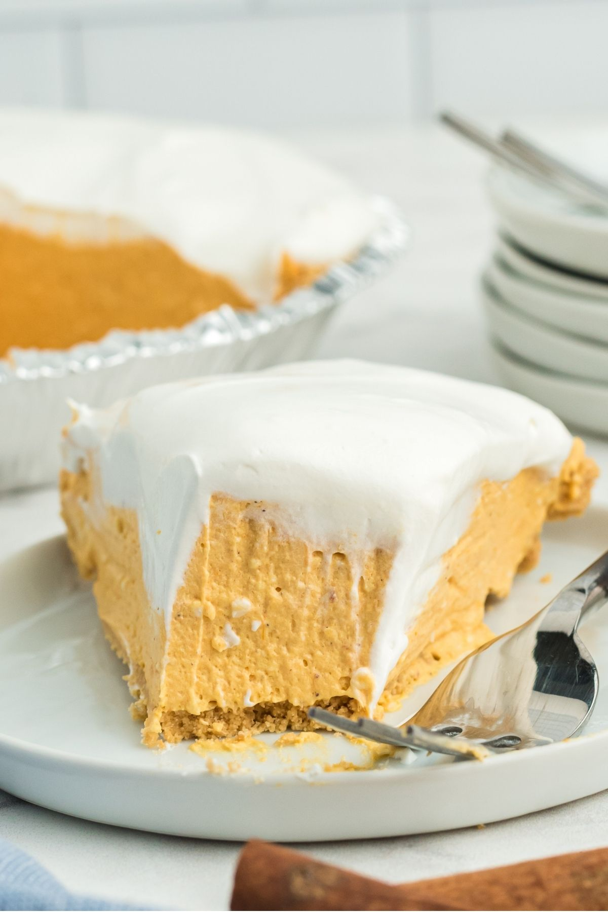 slice of no bake pumpkin pie with a bite out and cool whip on top