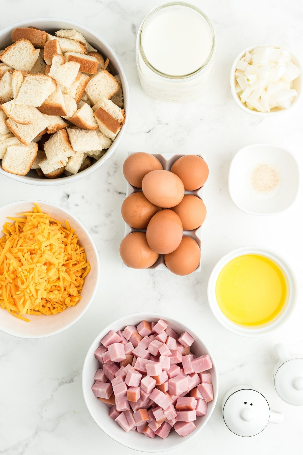ingredients on white counter: cubed bread, milk, chopped onions, seasoning, melted butter, 8 brown eggs, diced ham, shredded cheddar cheese