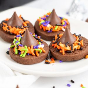 four chocolate cookies with Hershey kisses and sprinkles