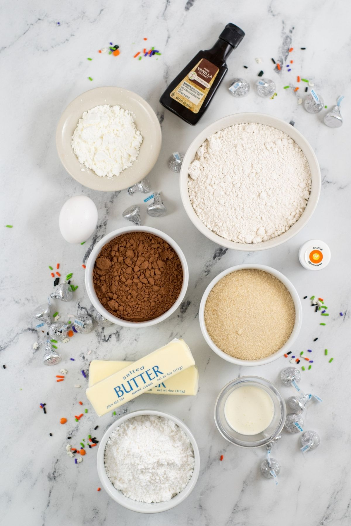 ingredients on white counter: vanilla, Hershey's kisses, egg, orange gel food coloring, flour, corn starch, cocoa powder, cream, and butter