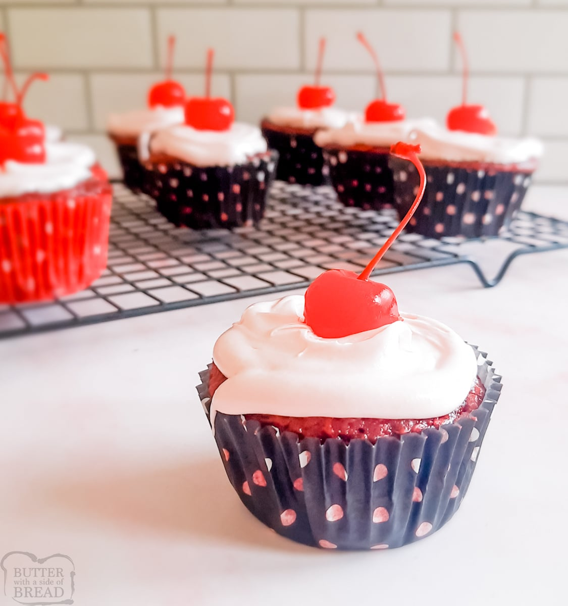 cherry cola cupcakes with white frosting and a cherry on top