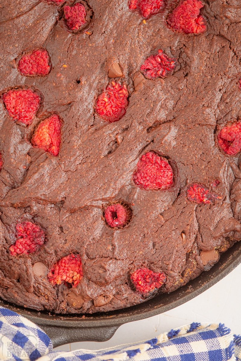 close up of raspberry brownies in a cast iron skillet