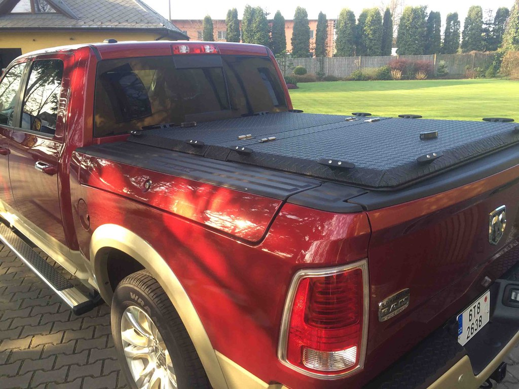 A Black Aluminum Tonneau Cover On A Dodge Rambox A Red
