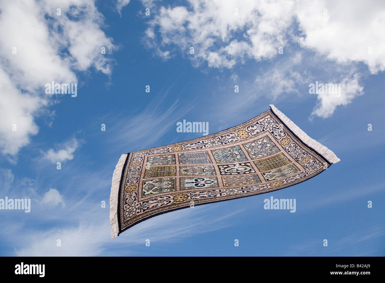 Magic carpet flying across blue sky with white clouds Stock Photo     Magic carpet flying across blue sky with white clouds