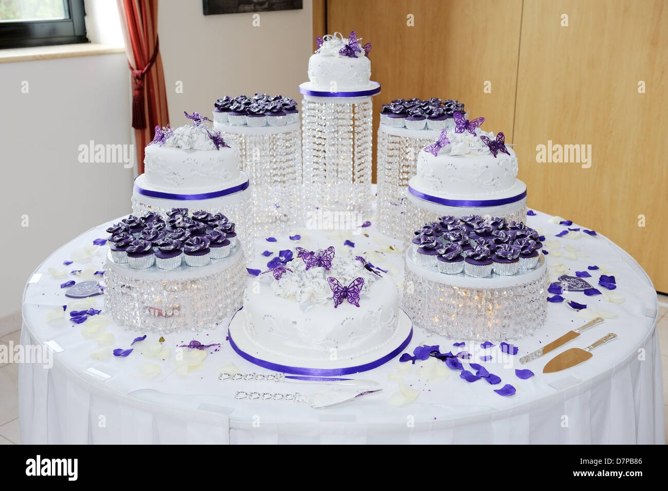 Huge wedding white and purple wedding cake at reception decorated     Huge wedding white and purple wedding cake at reception decorated with  petals and butterflies