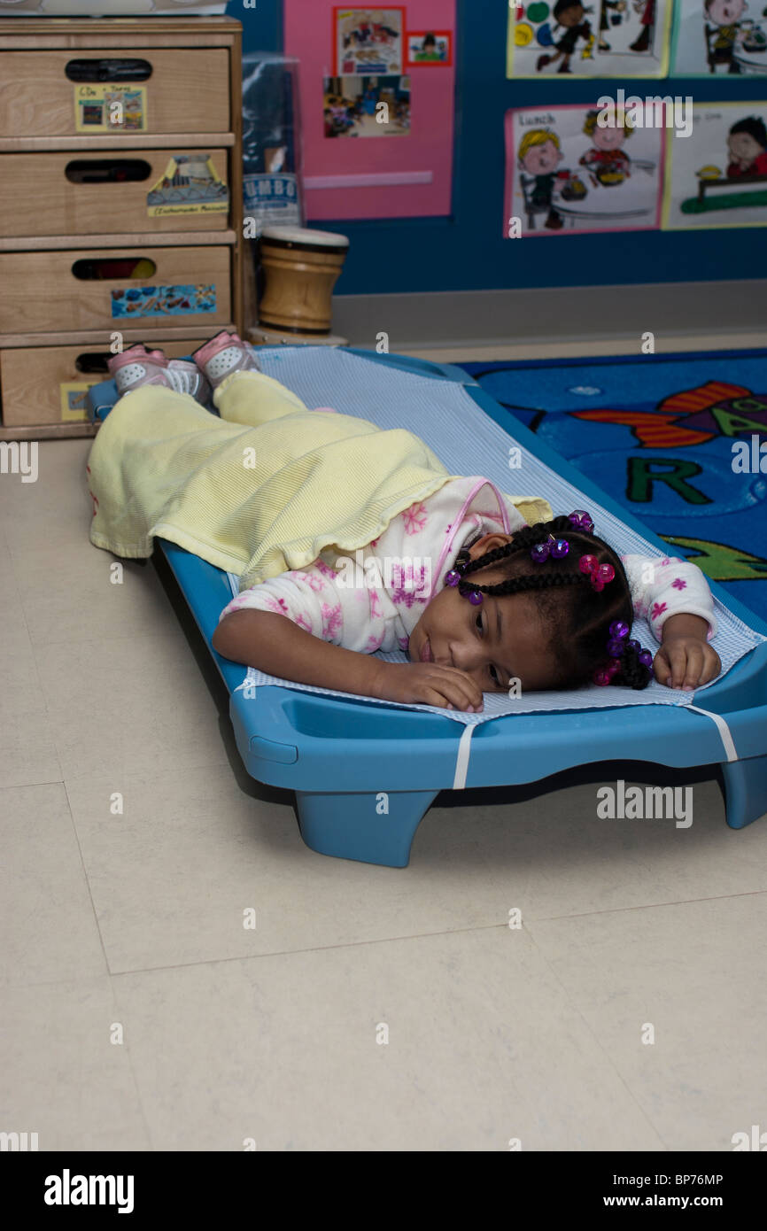 4 Year Old Preschool Girl Lying On A Cot During Nap Time