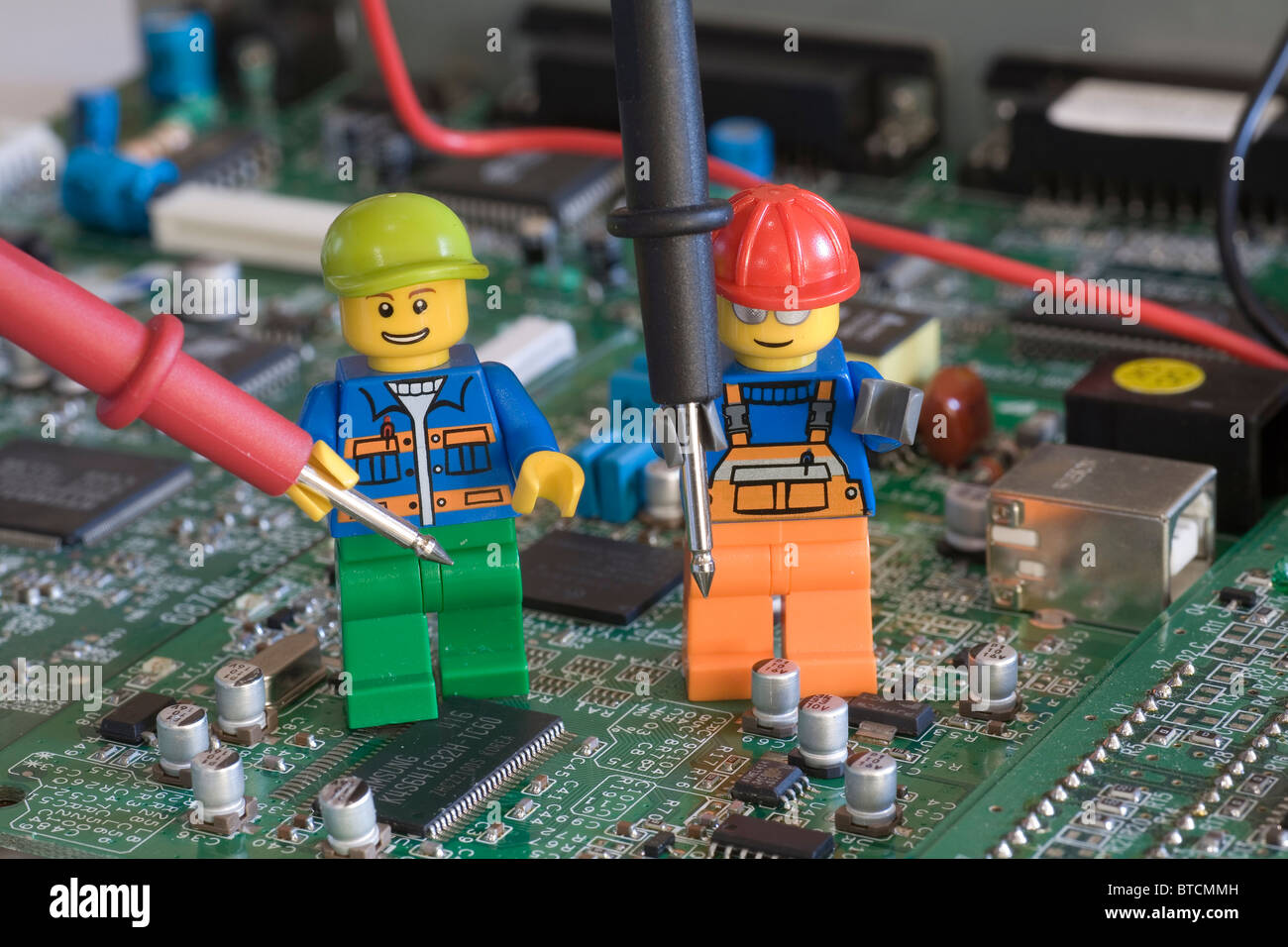Lego engineers on an electronic circuit board with testing probes     Lego engineers on an electronic circuit board with testing probes