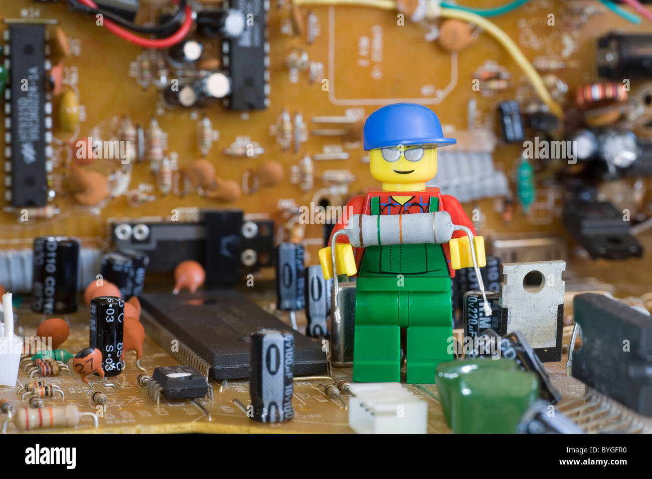 Lego engineer on an electronic circuit board holding an electronic     Lego engineer on an electronic circuit board holding an electronic resistor  component