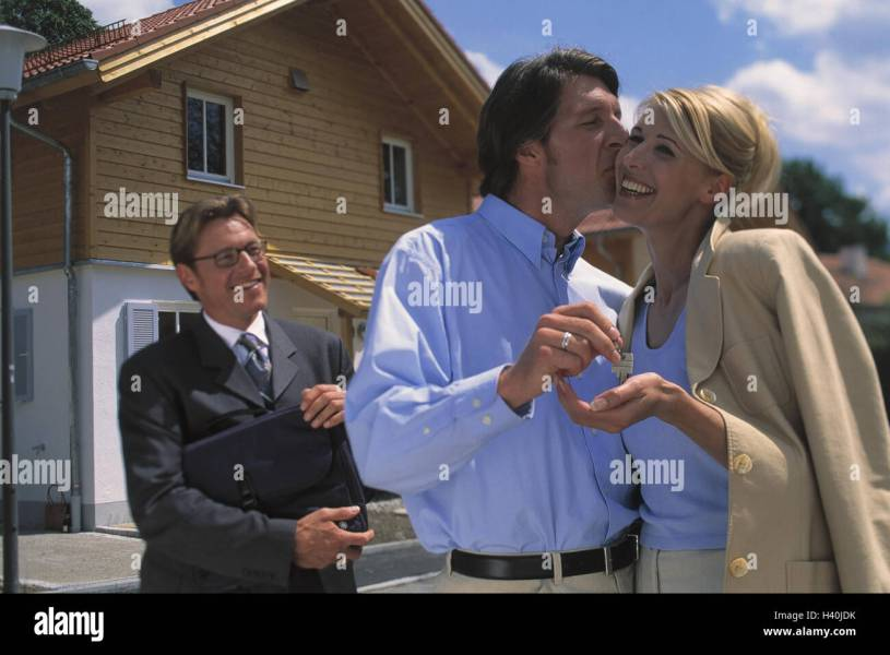 Estate agents  couple  happily  kiss  cheek  key discharge  outside     Estate agents  couple  happily  kiss  cheek  key discharge  outside  house   new building  real estate  real estate seller  businessman  broker  man