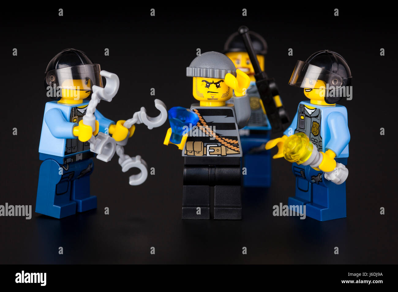Tambov  Russian Federation   August 27  2014 Lego night arrest     Tambov  Russian Federation   August 27  2014 Lego night arrest  Three  police officers and robber with diamond on black background  Studio shot