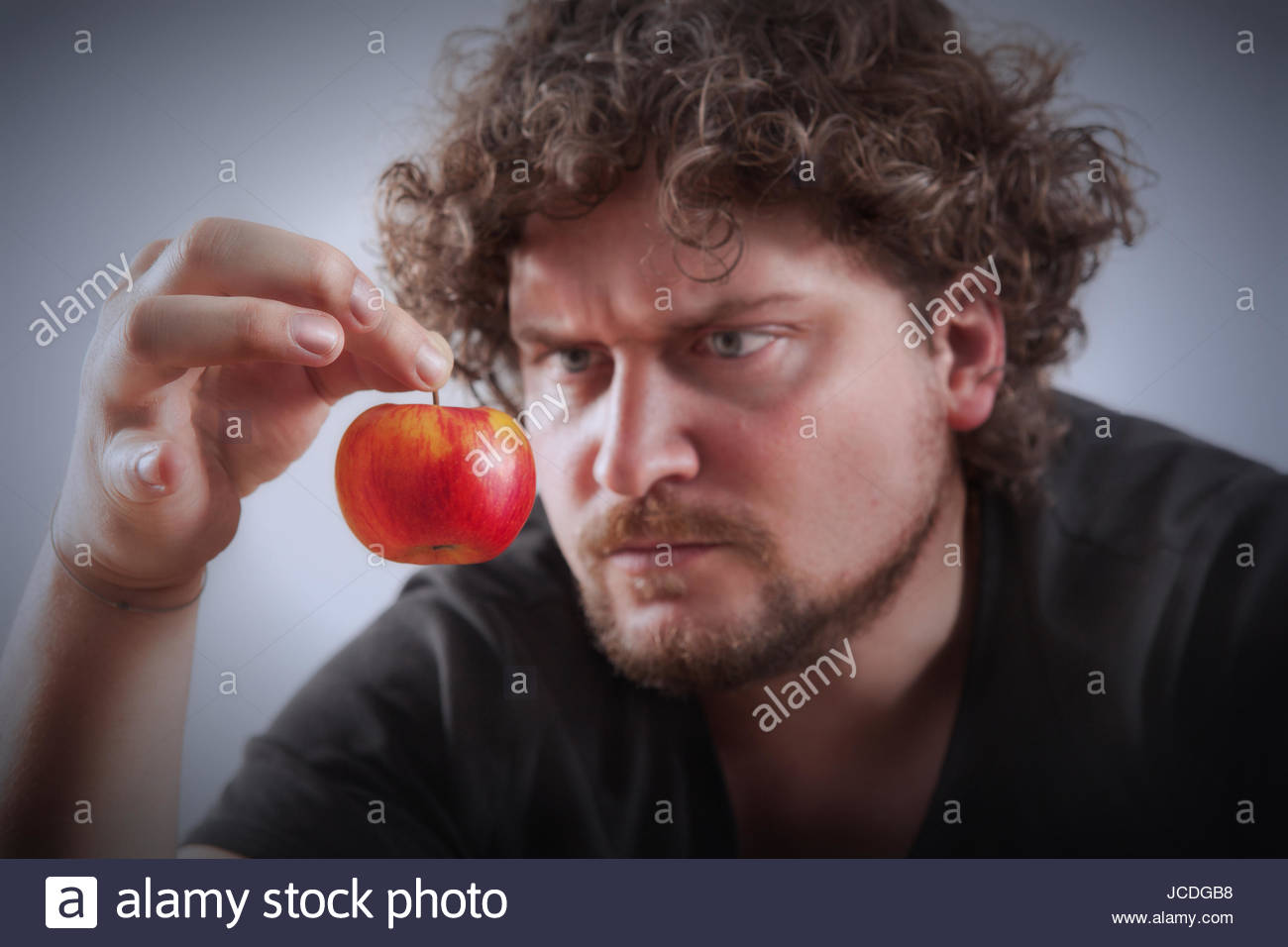 A man is looking very displeased about a little apple  Picture is     A man is looking very displeased about a little apple  Picture is toned  Apple is sharp   man in background is unsharp