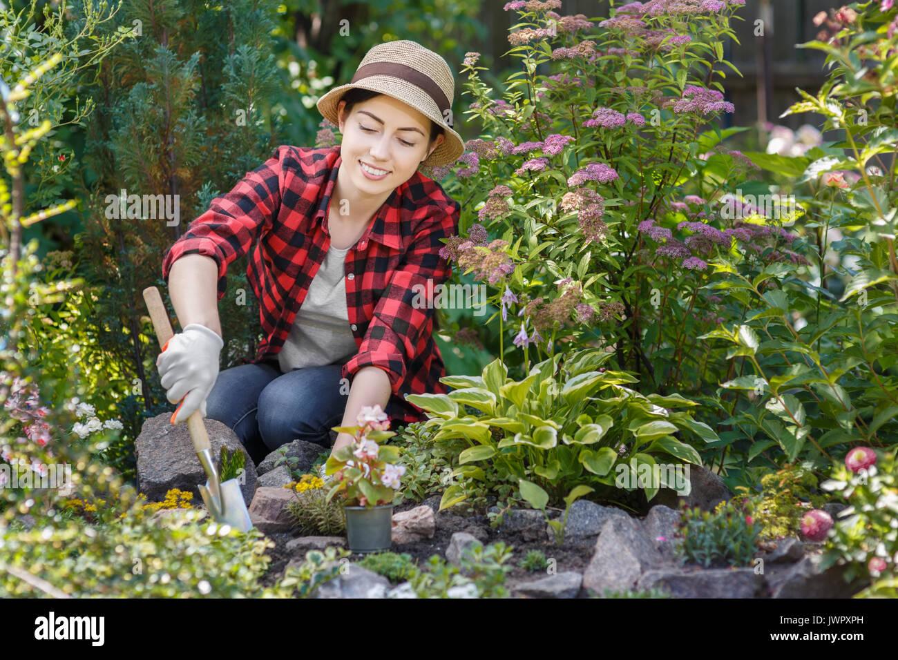 young woman gardener planting flowers in the garden ...