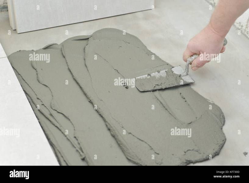 Laying Ceramic Tiles  Troweling mortar onto a concrete floor in     Laying Ceramic Tiles  Troweling mortar onto a concrete floor in preparation  for laying white floor tile