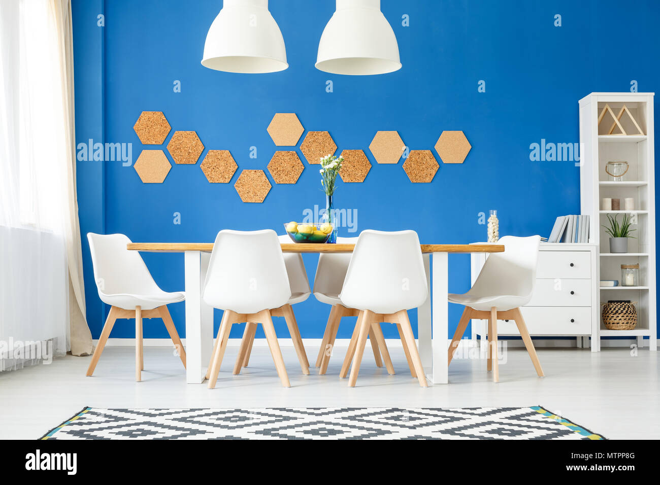 Stylish modern dining room with royal blue wall  wooden table  white     Stylish modern dining room with royal blue wall  wooden table  white designer  chairs  lamps  rug and honeycomb cork wall