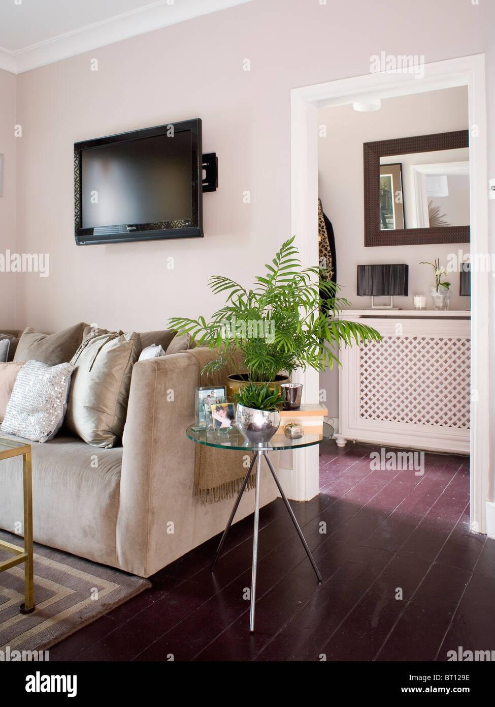 Fernsehen auf Wand über Beige Wildleder Sofa im modernen Wohnzimmer mit grünem Farn im Topf auf