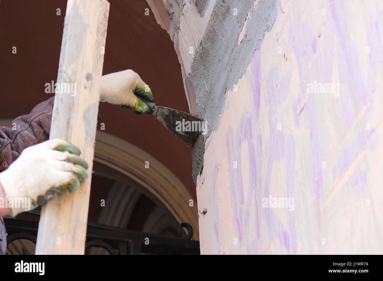 Bauarbeiter tragen Arbeitnehmer insgesamt mit Wand verputzen
