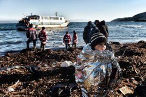 Criança é resgata por voluntários na ilha de Lesbos, na Grécia. Os imigrantes recebem agasalhos e cobertores – Foto: Aris Messinis/AFP