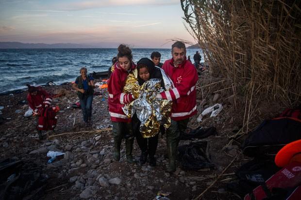 Voluntários socorrem mulher imigrante na Ilha de Lesbos, na Grécia – Foto: Santi Palacios/AP