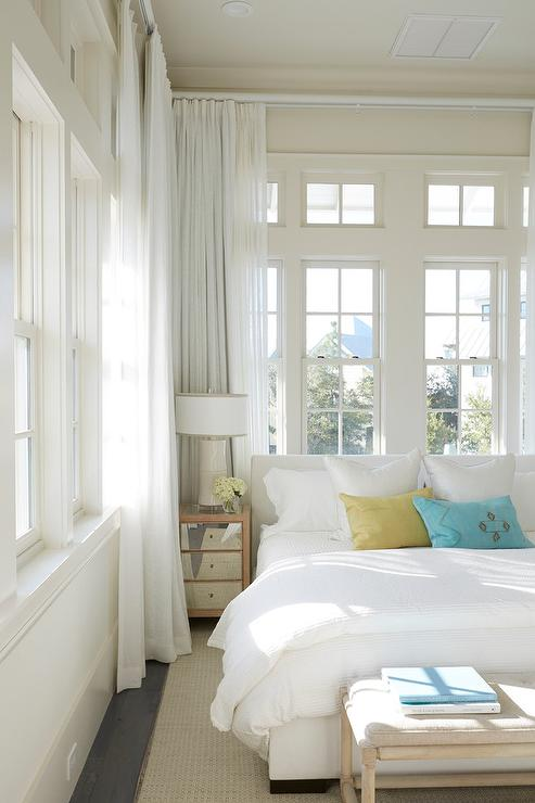 Beach Style Bedroom With White Upholstered Bed And Small