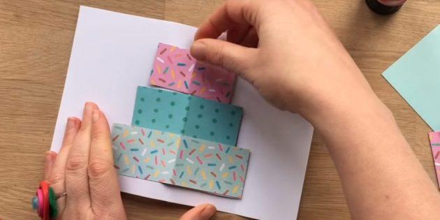 Schneiden Sie drei Rechteck aus farbigem Papier in der Größe auf die Schicht des zukünftigen Kuchens