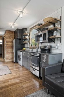 10 Amazing Shipping Container Home Designs to Make You Wonder Some of the wood edging on the outside  is similar to the wall next to the  refrigerator  while the same grey color of the cabinets is used outside for  a