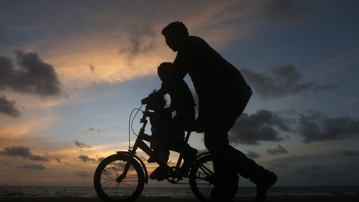 Carol Dweck Explains the False Growth Mindset   The Atlantic A man guides a child riding a two wheel bike  It s sunset  and