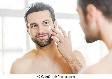 Skin care. Handsome young shirtless man applying cream at...