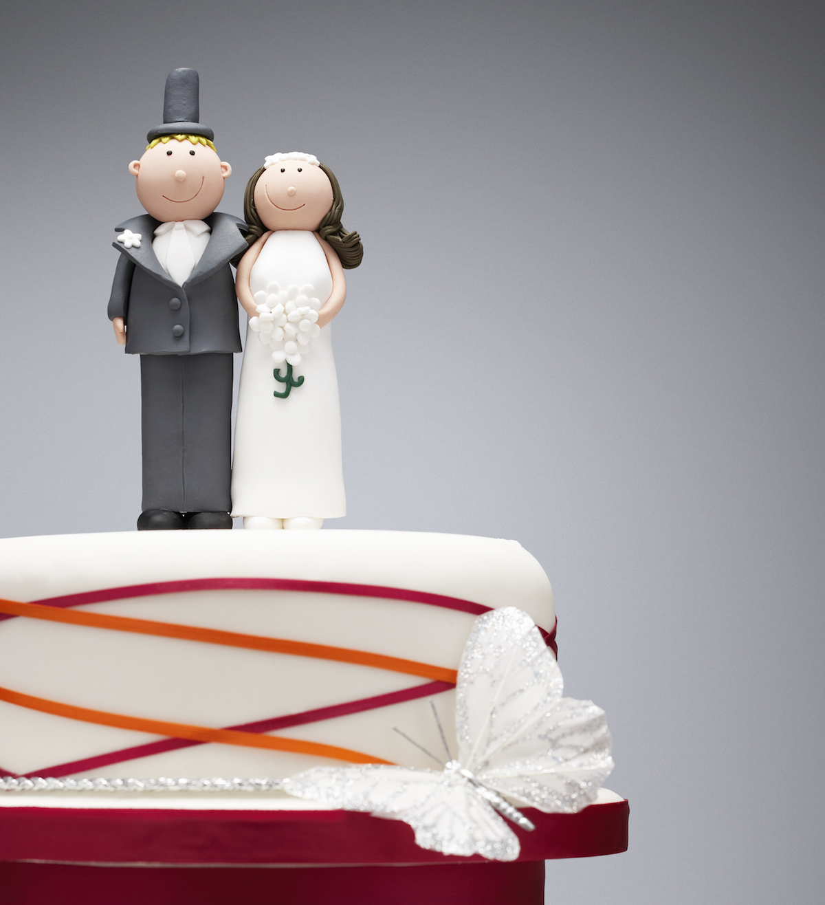 How to Freeze Your Wedding Cake Topper   Boston Magazine Comical bride and groom figurines on top of wedding cake via Shutterstock