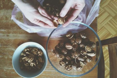 decorticate   EyeEm Decorticating walnuts on wooden table  Human Hand High Angle View Human  Body Part One Person