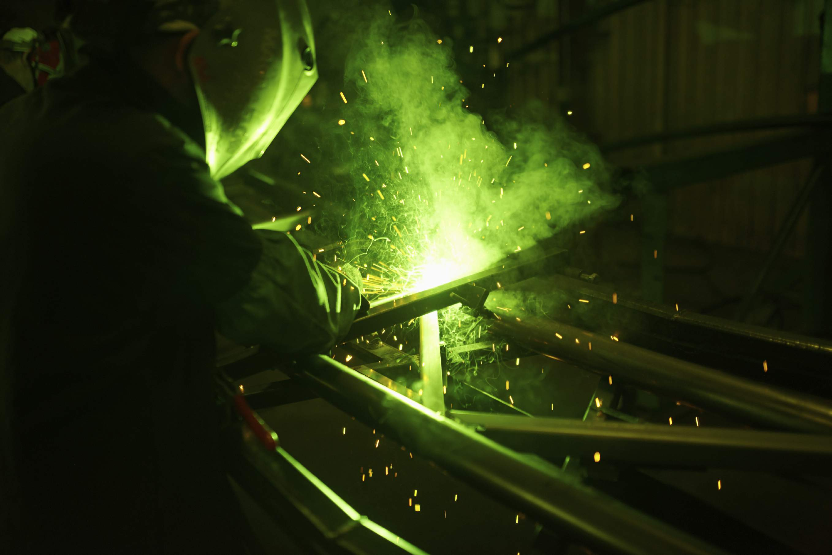 An image of a person welding the welder is illuminated by the green welding light, it looks really cool