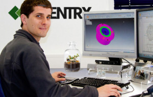 An image of a man sitting in front of his computer monitor, he is turned to look at the camera and is slightly smiling. On the monitor is a CAD part