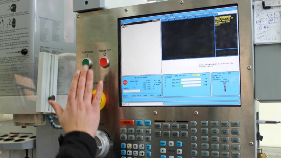 an up-close image of a CNC Milling Machine used by Centrx inc., A Pittsburgh contract manufacturer, The image is showing a control panel with lots of buttons and a LCD screen, there is also a mans hand pushing an on button.