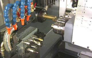 an upclose Image of a CNC Milling machine it has blue water hoses with orange tips it's also showing the silver and brass cutting heads, it looks like an awesome metal forming monster. L.O.L.