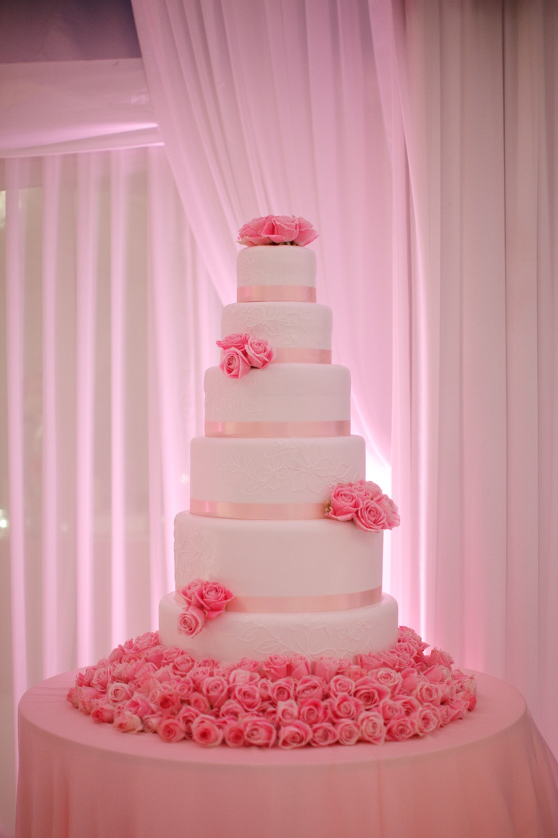 Cakes   Desserts Photos   Pink Rose Cake   Inside Weddings Tall white cake with pink ribbon and pink roses