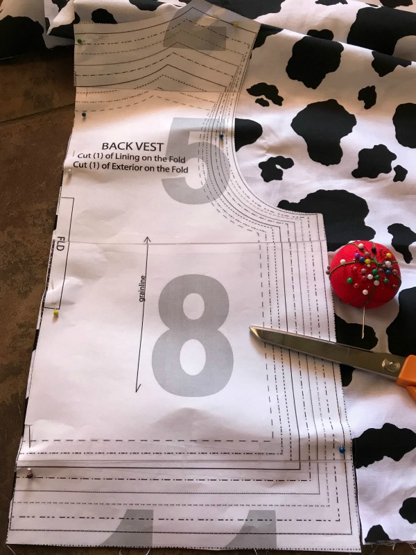 Cut woody's vest using pattern and folded over cow print fabric