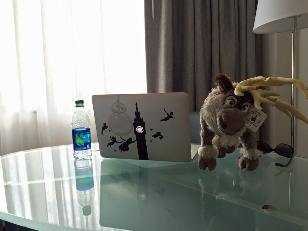 Glass desk top with a water bottle, Sven reindeer stuffed animal and macbook sitting on it.