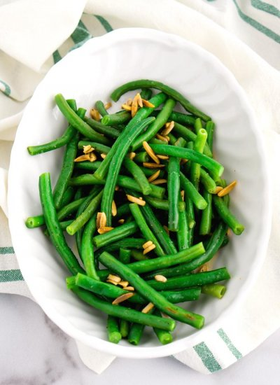 Overhead picture of green beans almandine in a white serving bowl.